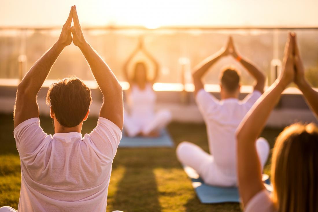 Leute, die Yoga unter freiem Himmel machen