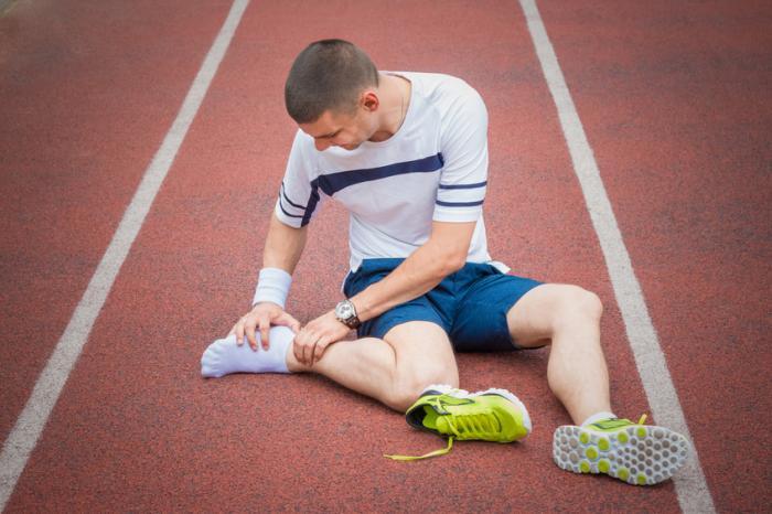 Спортист разглежда болезнената си пета.