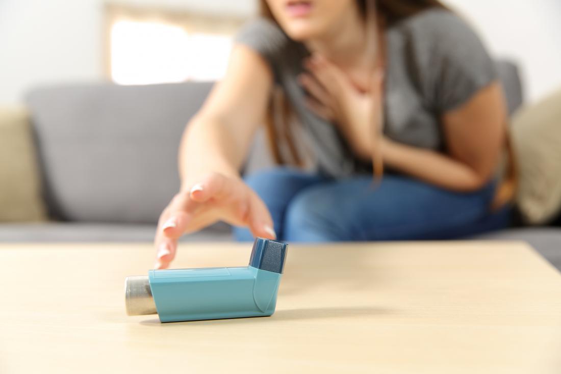 Femme souffrant d'asthme atteignant pour la pompe à la recherche d'un remède à la maison d'urgence pour une crise d'asthme