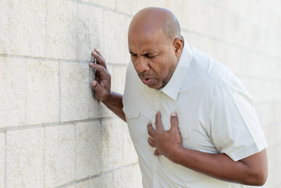 [homem encostado a uma parede tendo um ataque cardíaco]