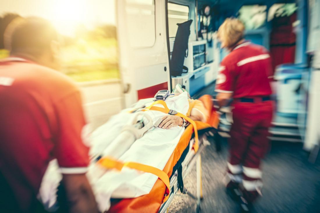 [paramédicos empurrando um paciente para uma ambulância]