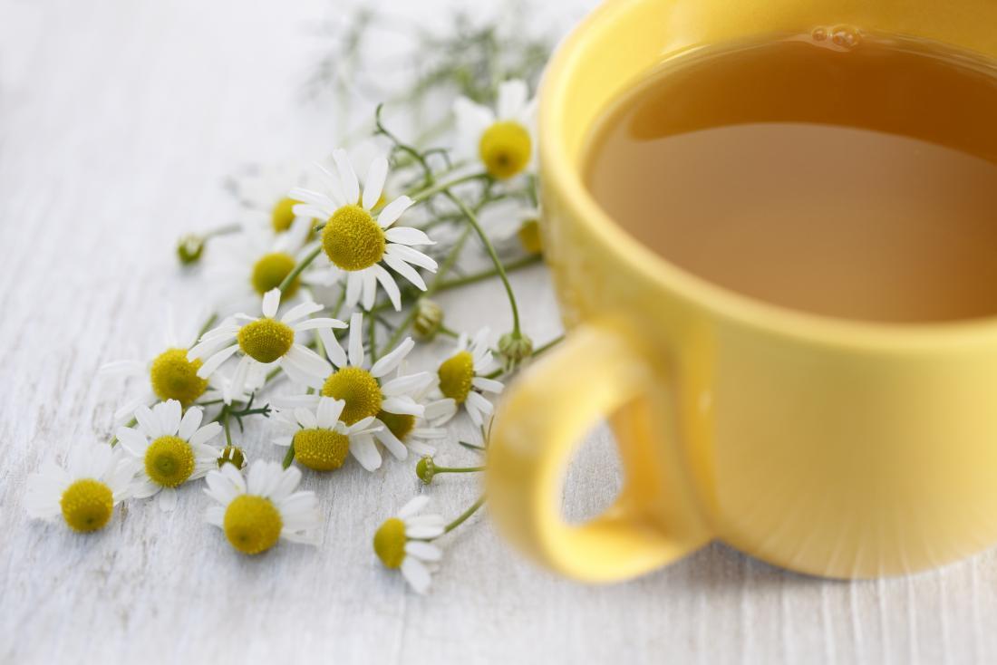 uma xícara de chá de camomila com flores de camomila