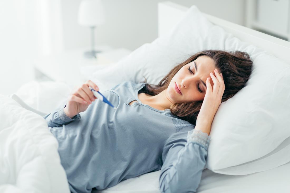 Mulher na cama, medindo a temperatura com febre.