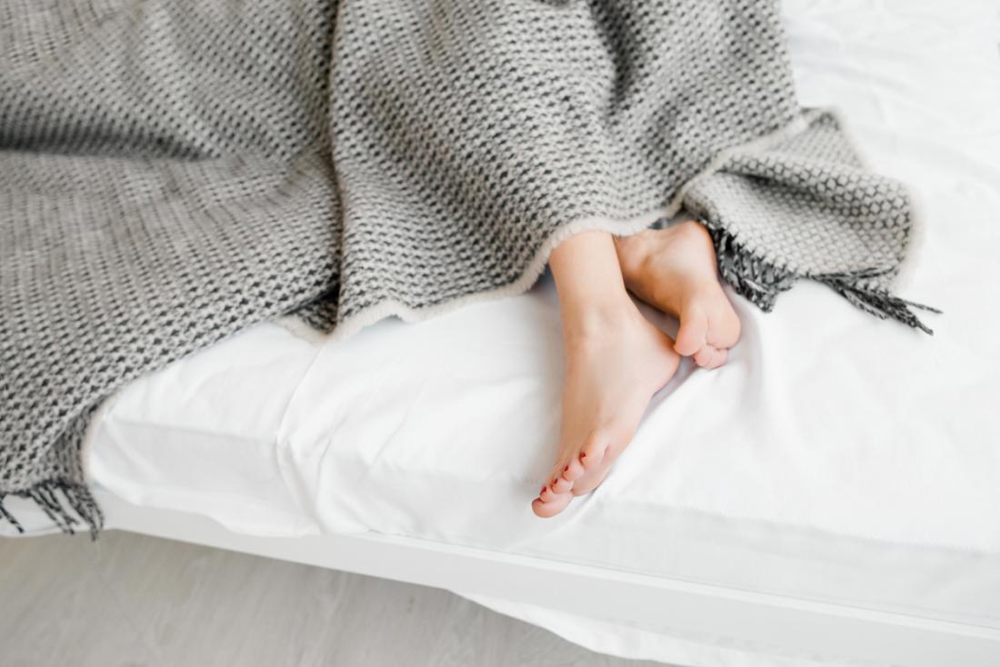 les pieds qui sortent de sous une couverture grise