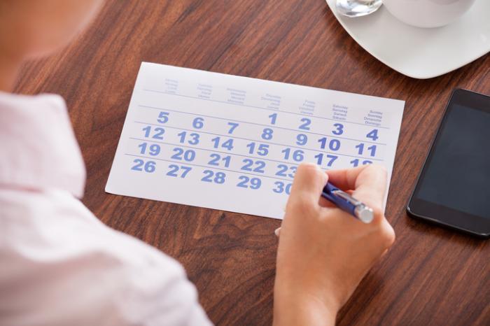 [Frau schaut auf den Kalender]