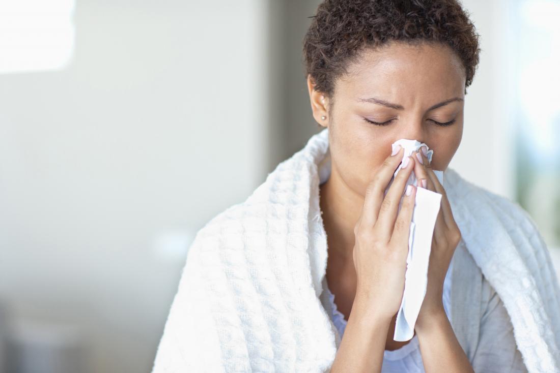 鼻の詰まりのために彼女のくしゃみを組織に刺す女性。