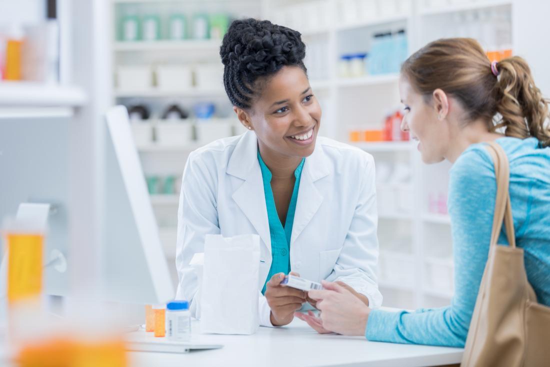 Pharmacien discutant de différents médicaments avec le patient.