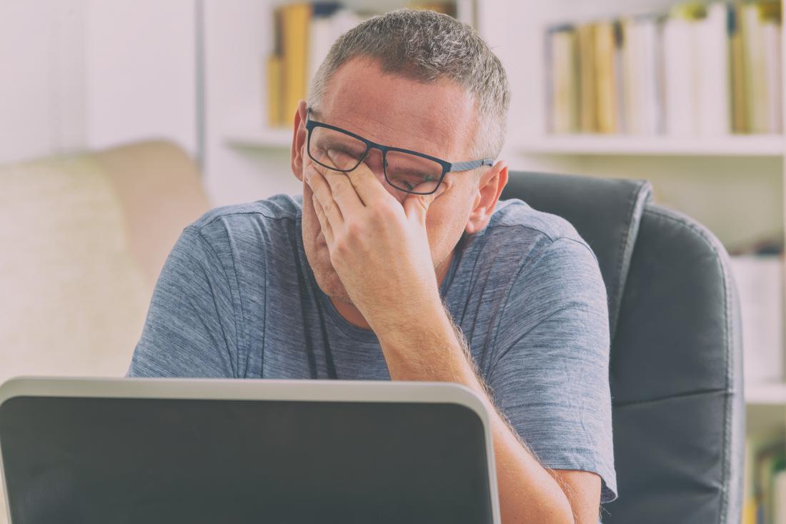 ストレスと疲れた男はラップトップの目の前で目をこすります。