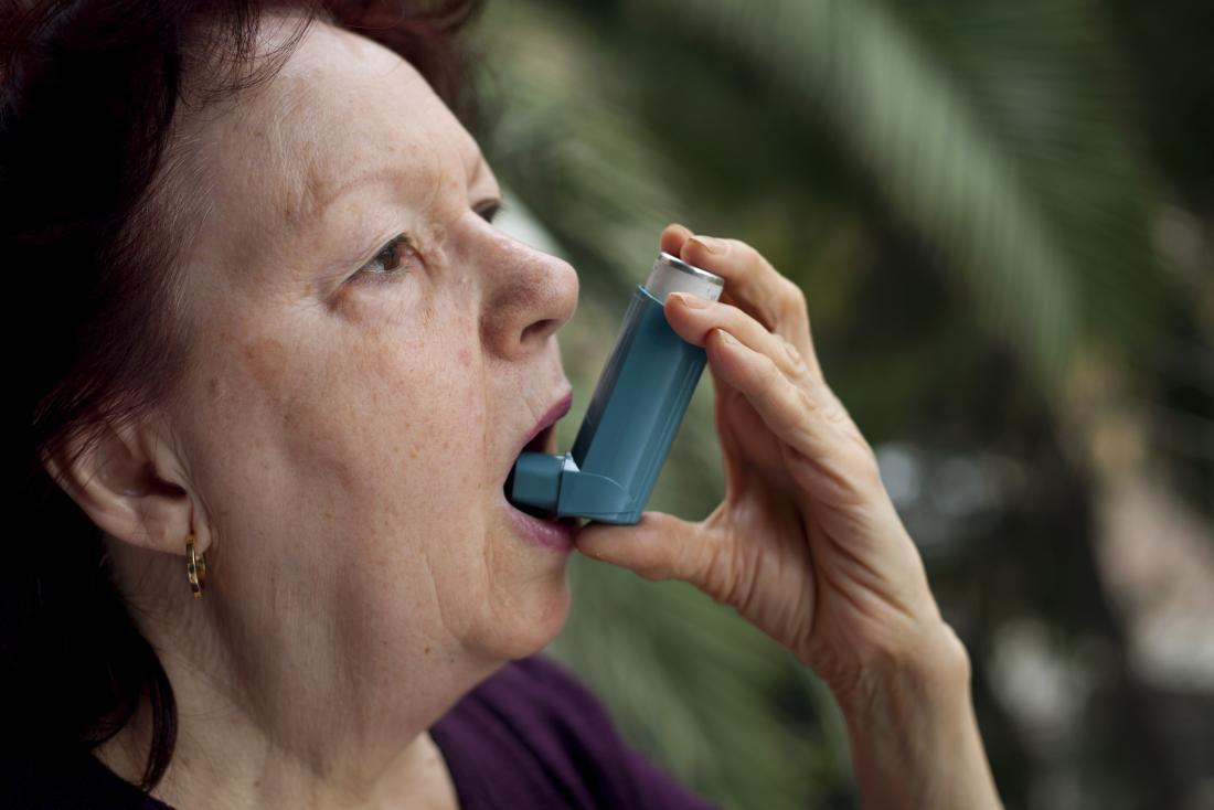 気管支拡張剤吸入器を使用する女性