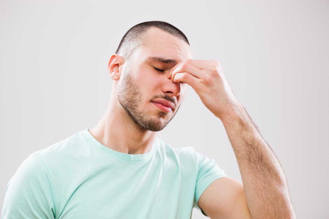 Homme souffrant de maux de tête et de sinusite tenant des sinus dans la douleur.