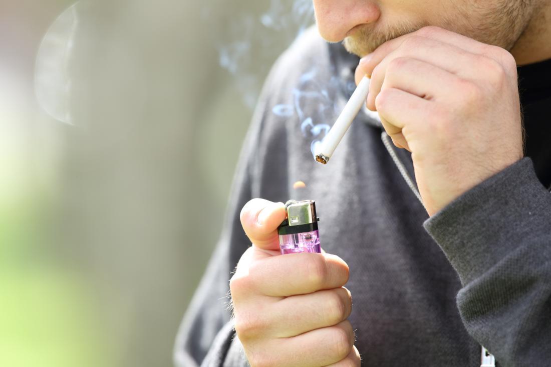Personne utilisant un briquet pour fumer une cigarette.