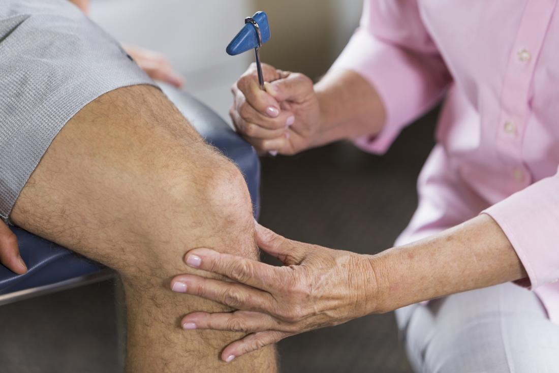 fisioterapeuta testando pacientes reflexos na articulação do joelho.