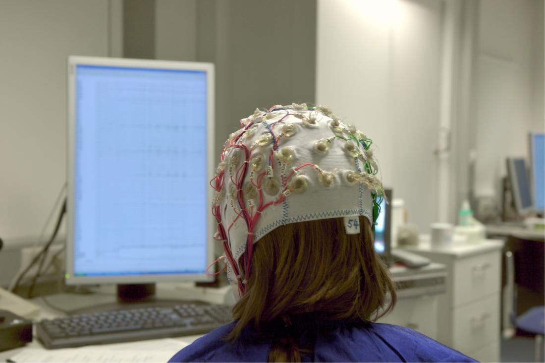 脳波をしながら画面の前に座っている若い女性