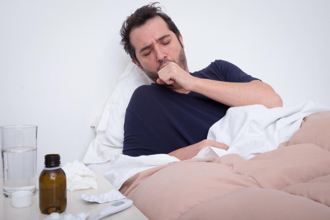 Mann im Bett hustet, erlebt Lungenentzündung.