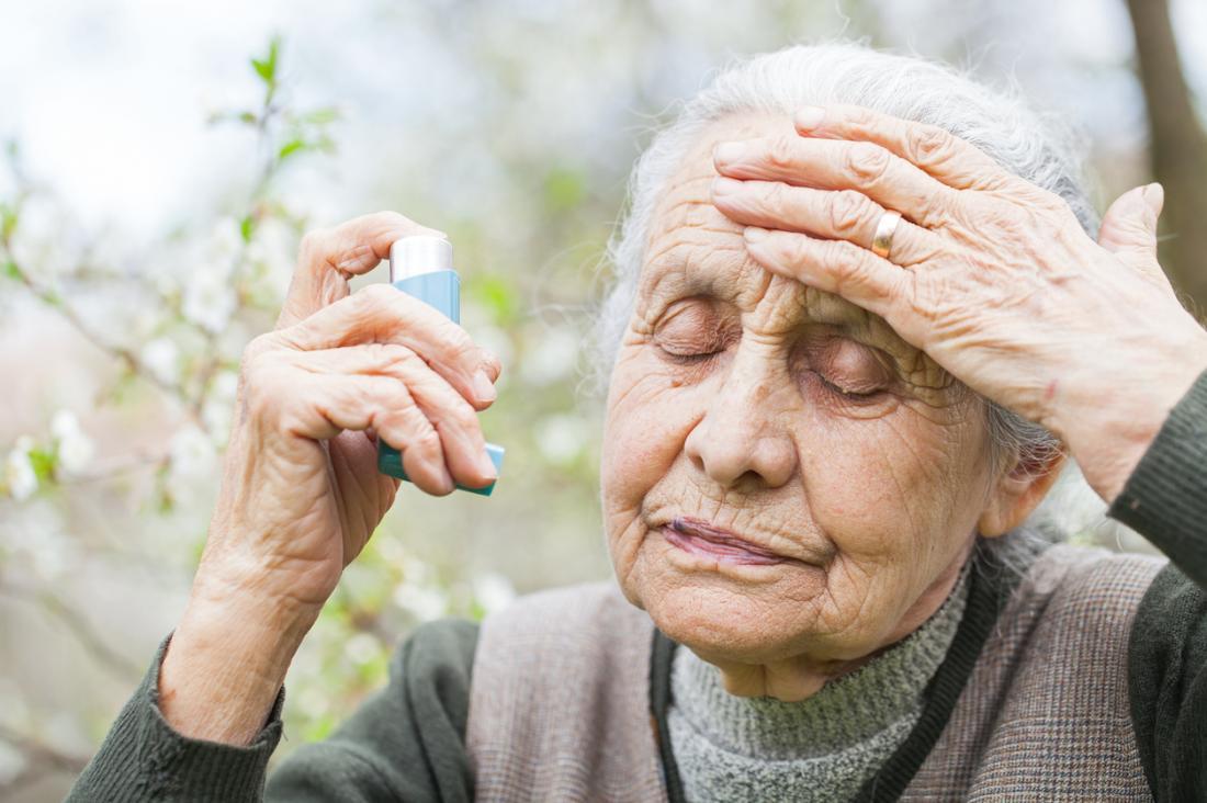 Ältere Frau, die Bronchodilatorinhalator während des Asthmaanfalls verwendet