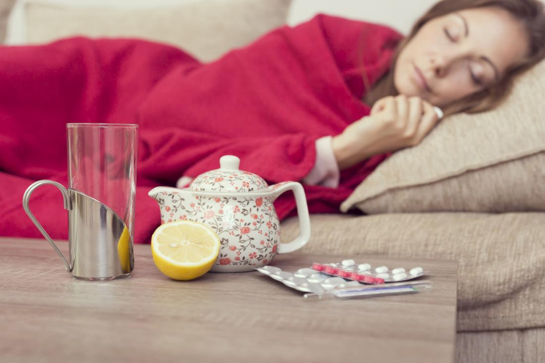 Stillstehende Frau beim Leiden an Grippe oder Erkältung, mit Zitronentee und Medikamenten.