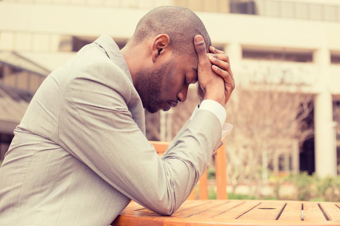 Betonter und deprimierter Mann, der seinen Kopf, erfahrenes allgemeines Anpassungssyndrom hält.