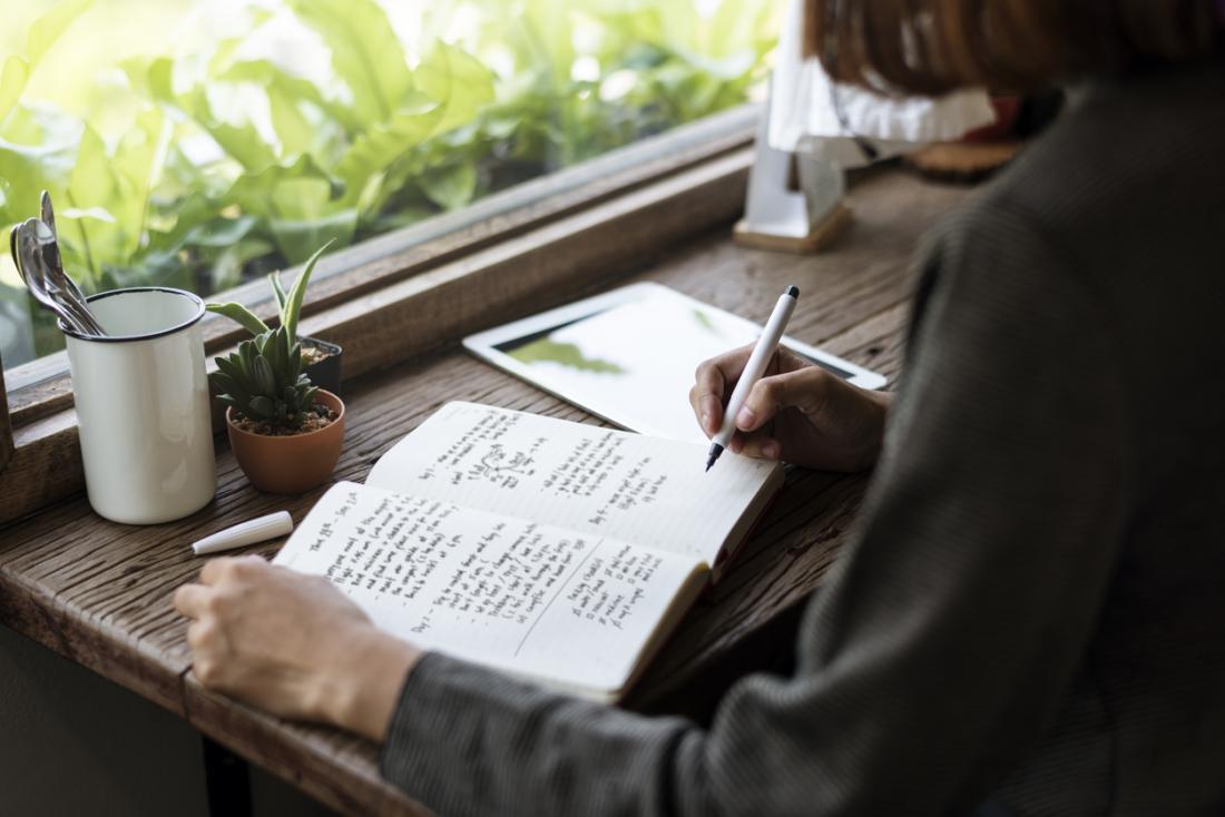Frau von Pflanzen umgeben, in ein Tagebuch oder Tagebuch schreiben
