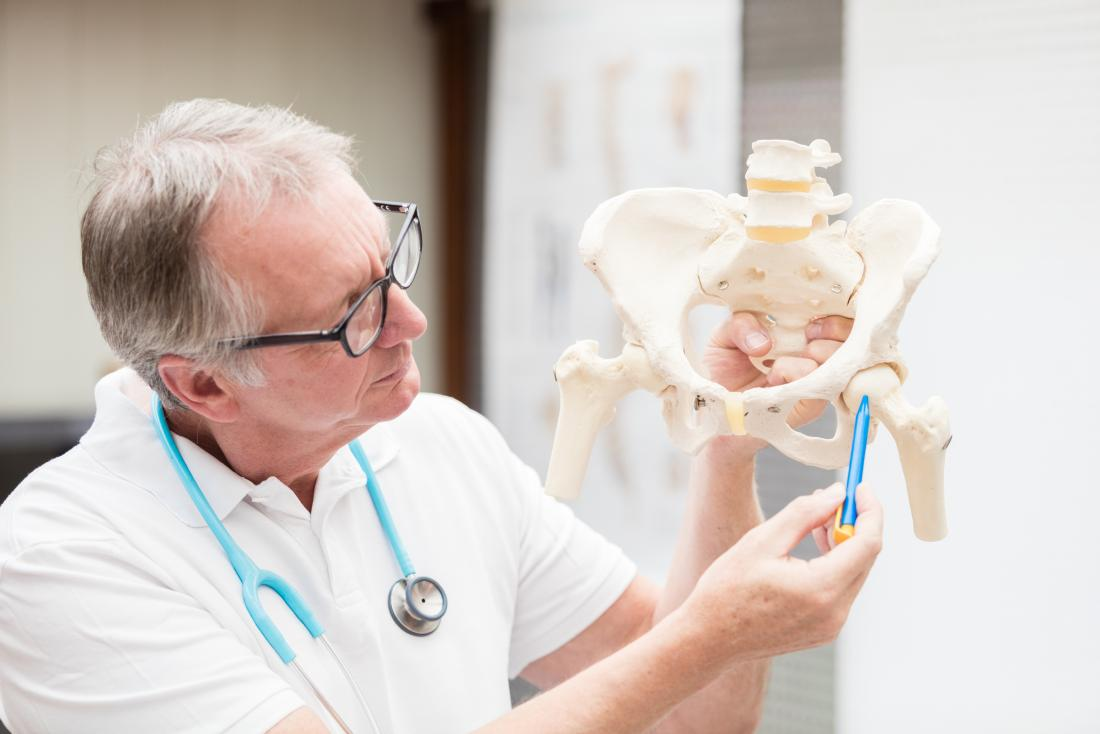 解剖学的モデルの股関節を指して腸骨嚢炎を説明する医師。