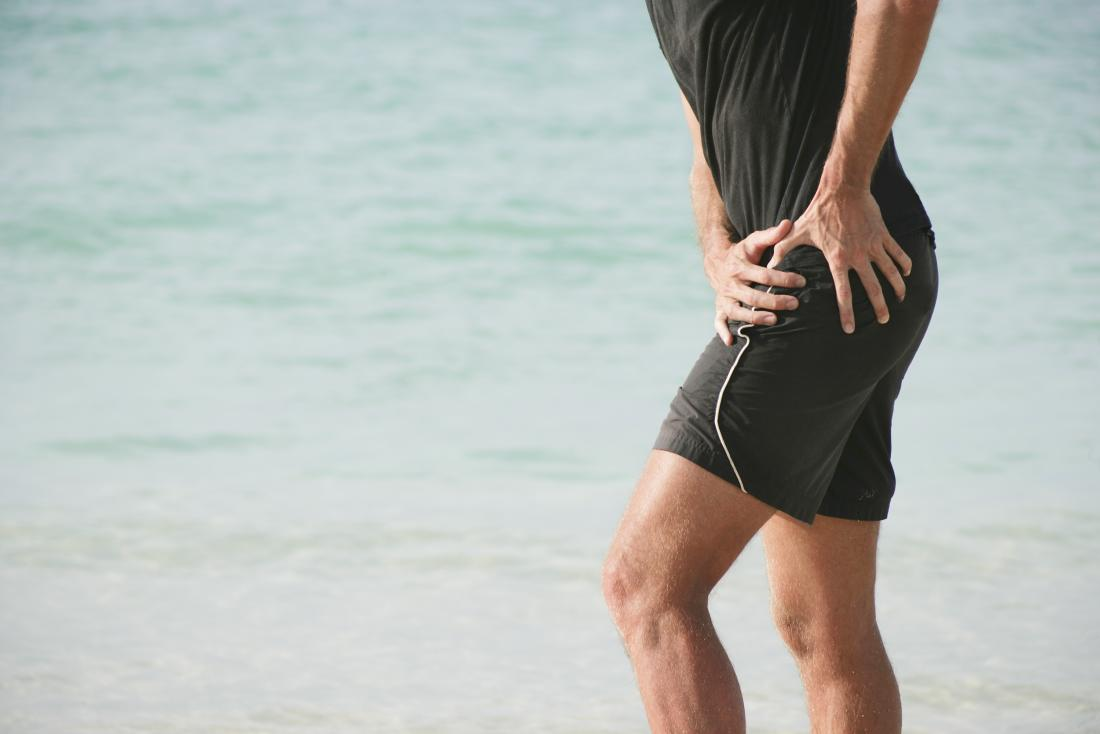 Läufer, der vor Schmerz seine Hüfte umklammert.