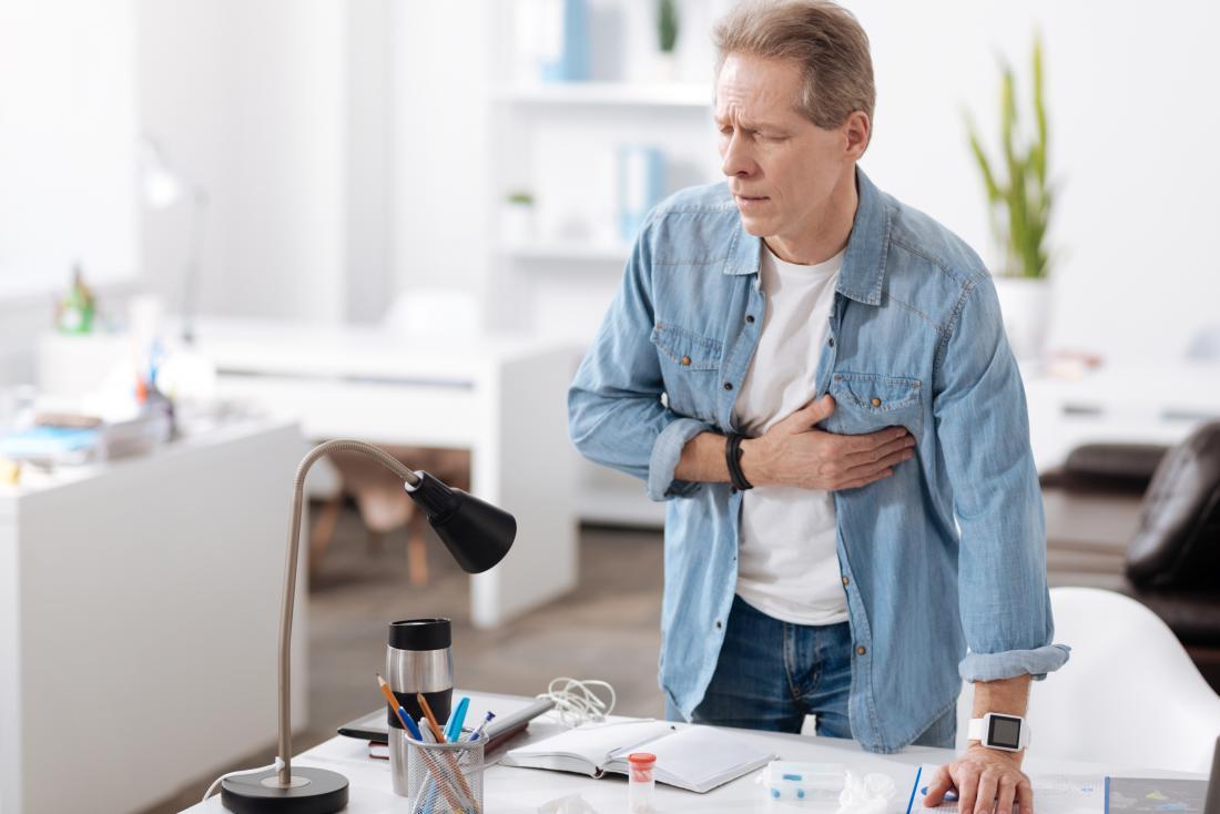 Mann, der Herzschmerzen der Brustschmerzen hat, und Herzinfarkt am Schreibtisch