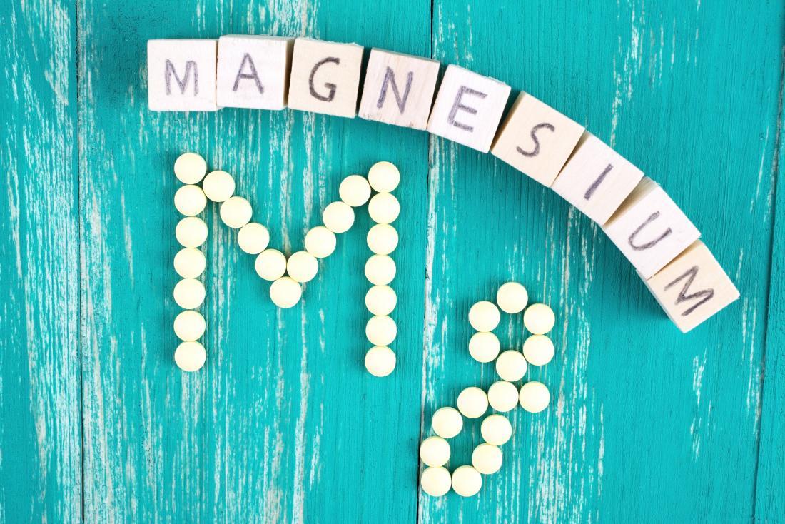 Magnésio soletrado para fora com blocos de madeira no fundo de madeira turquesa com comprimidos redondos de magnésio soletrando Mg