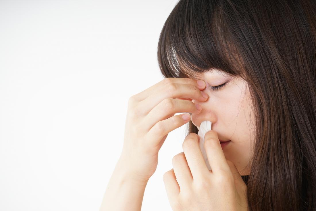 Mulher com hemorragia nasal colocando tecido na narina.
