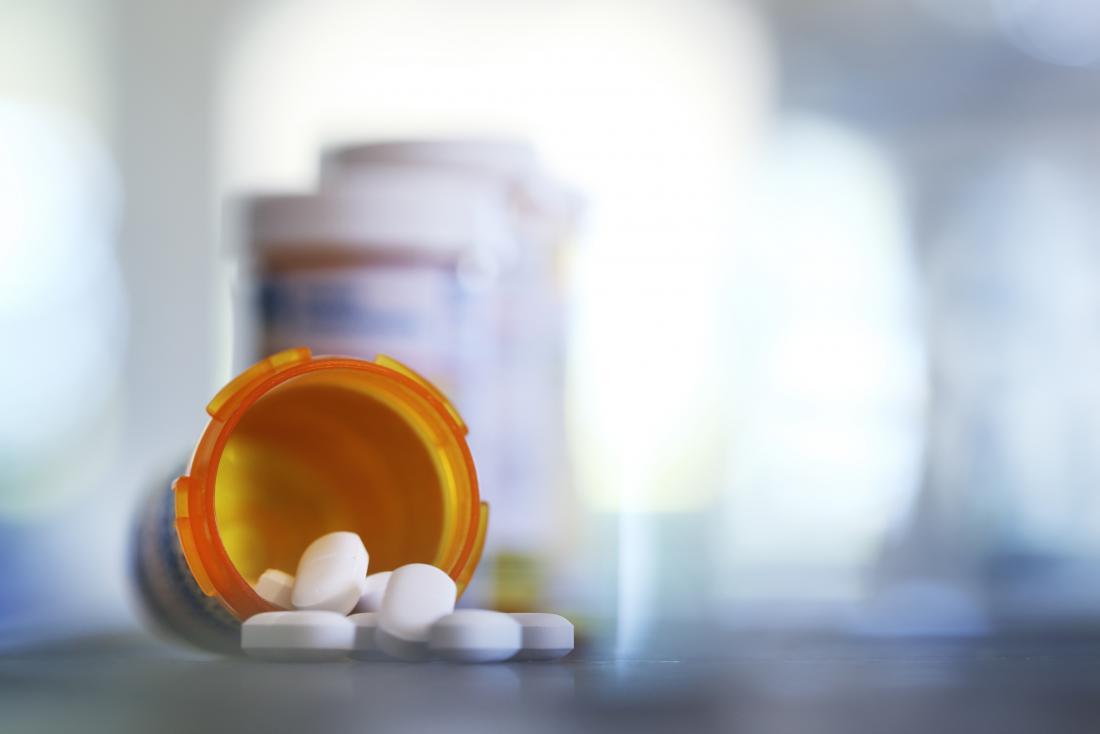 Pílulas antibióticas derramando fora do pote de medicação.