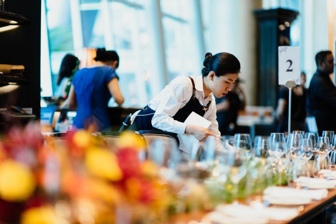 donna che fissa la tavola in un lavoro di catering