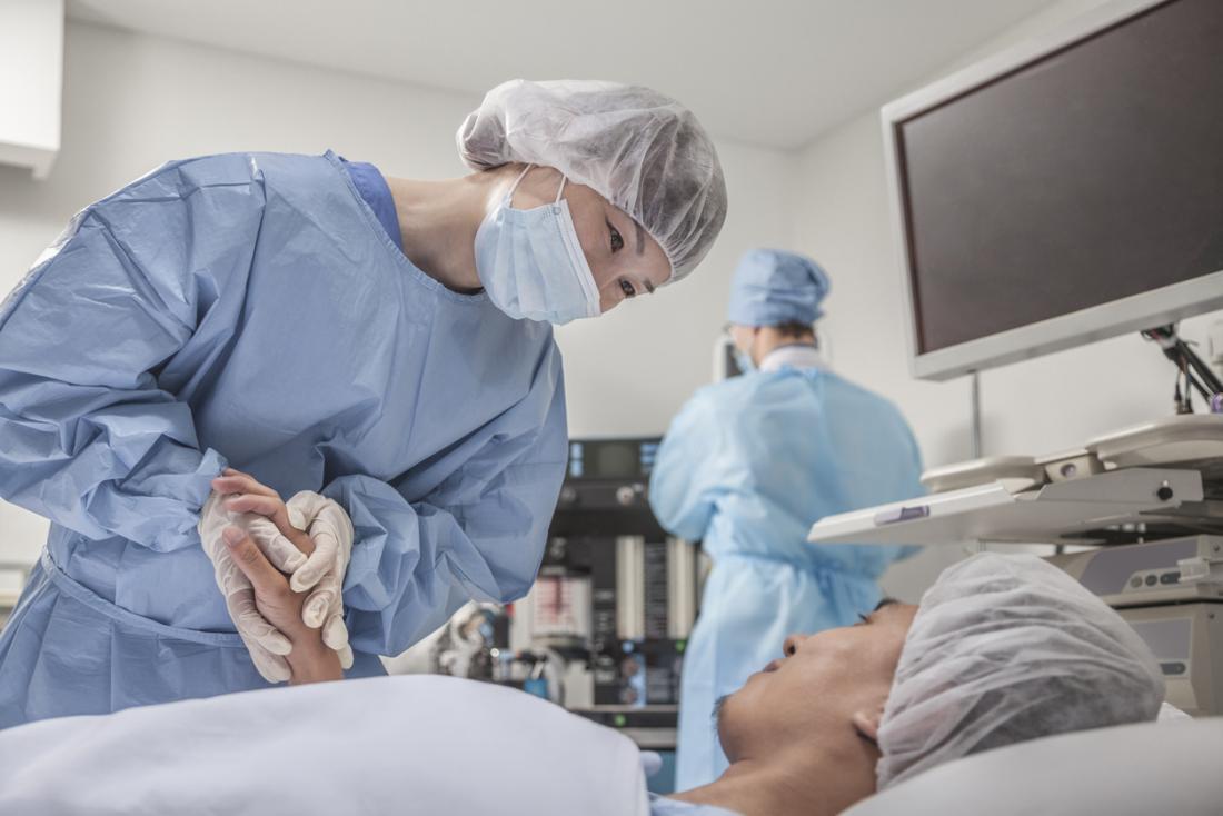 Homme sur le lit de la chirurgie, avec le chirurgien tenant sa main.