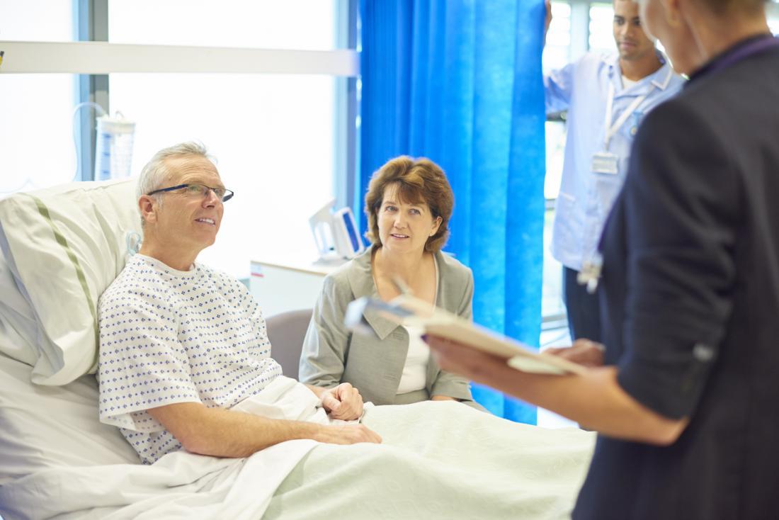 Người đàn ông trong giường bệnh nói chuyện với bác sĩ, phục hồi từ phẫu thuật.