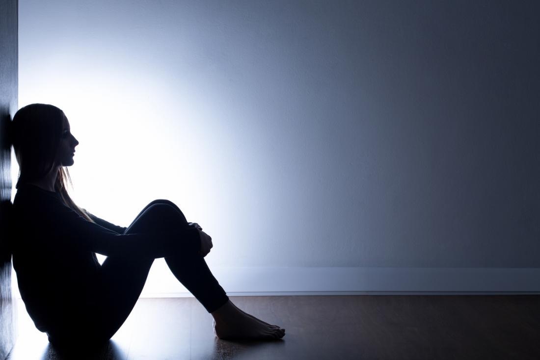 Fille assise sur le sol dans le noir