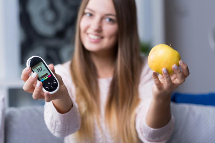 Une femme tient un glucomètre et une pomme.