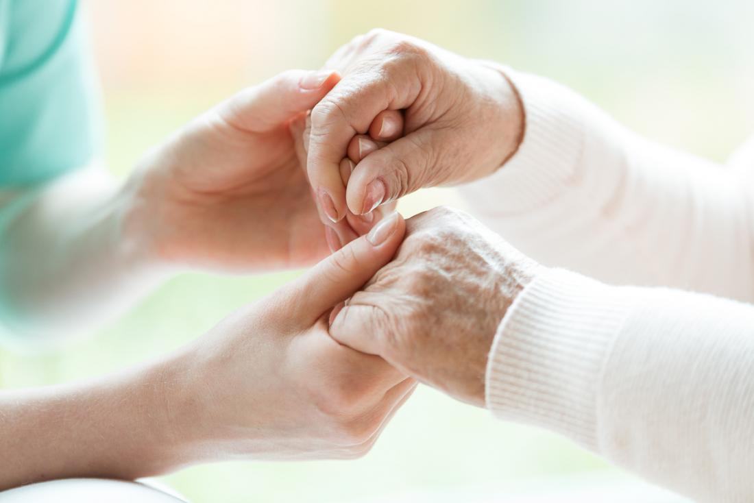 Senior avec Parkinson se tenant la main avec une infirmière.