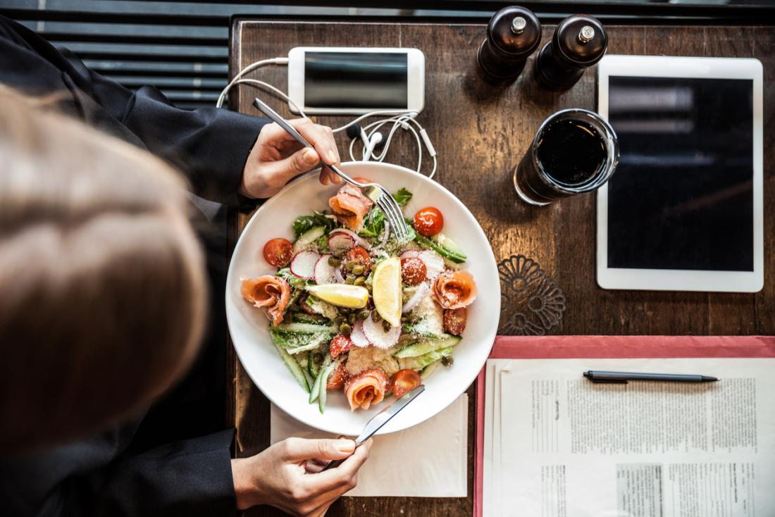 Person, die einen Salat mit Telefon, Tablette und Ordner auf Tabelle isst.