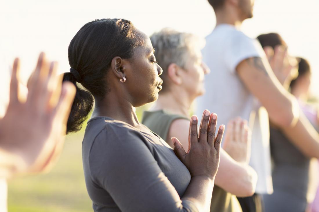 Übendes Yoga und Meditation der Frau draußen mit Gruppe.