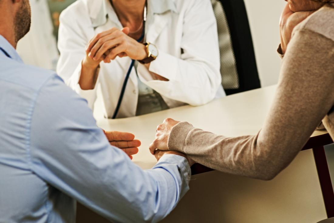 Händchenhalten der Paare, sprechend mit Doktor.