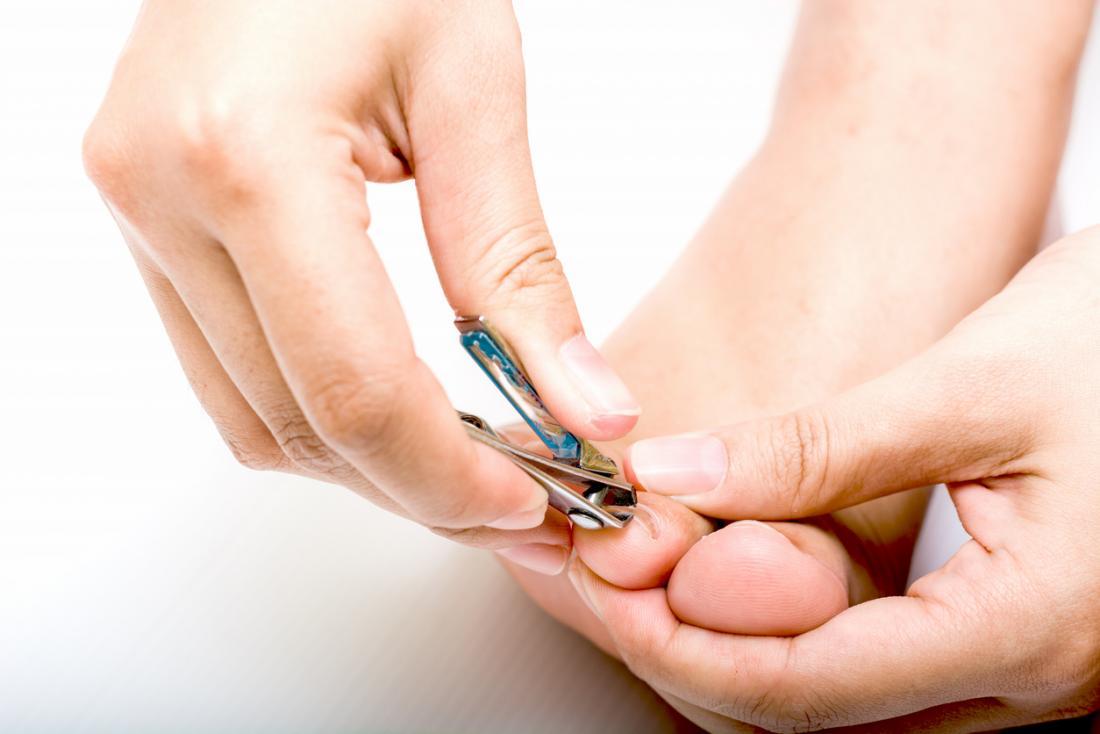 Persona che ritaglia le unghie dei piedi