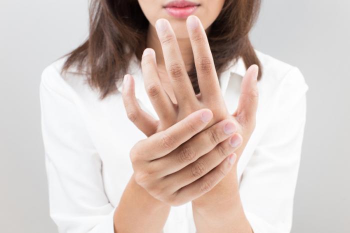 Une femme tient sa main engourdie.