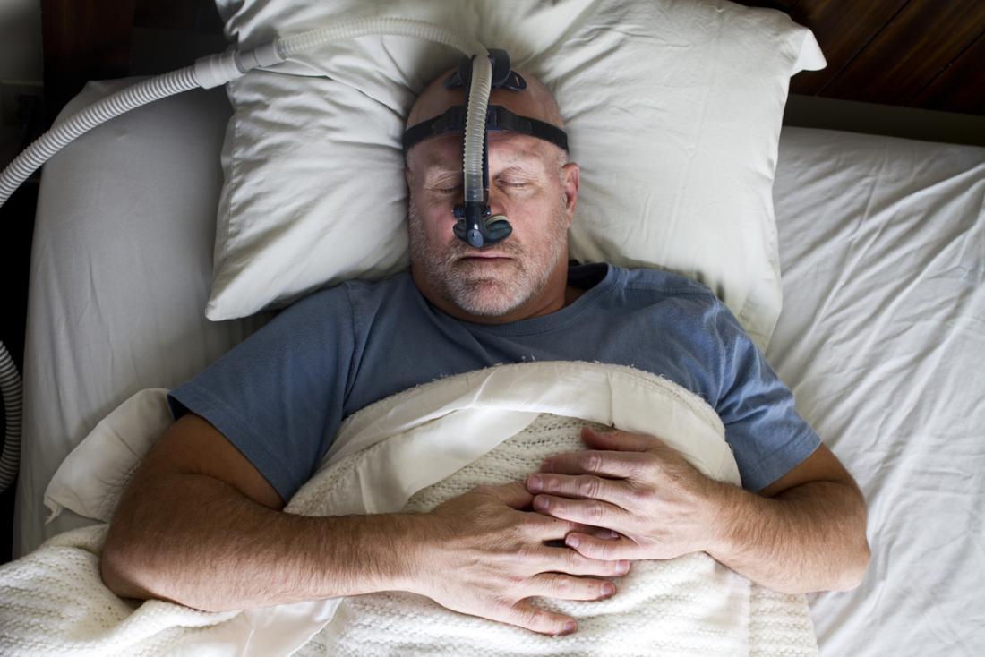Homme endormi avec masque de thérapie CPAP.