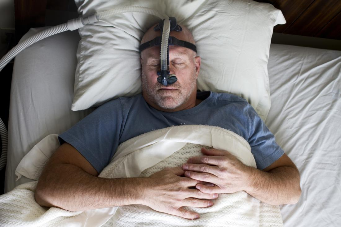 CPAP療法マスクを寝かした男。