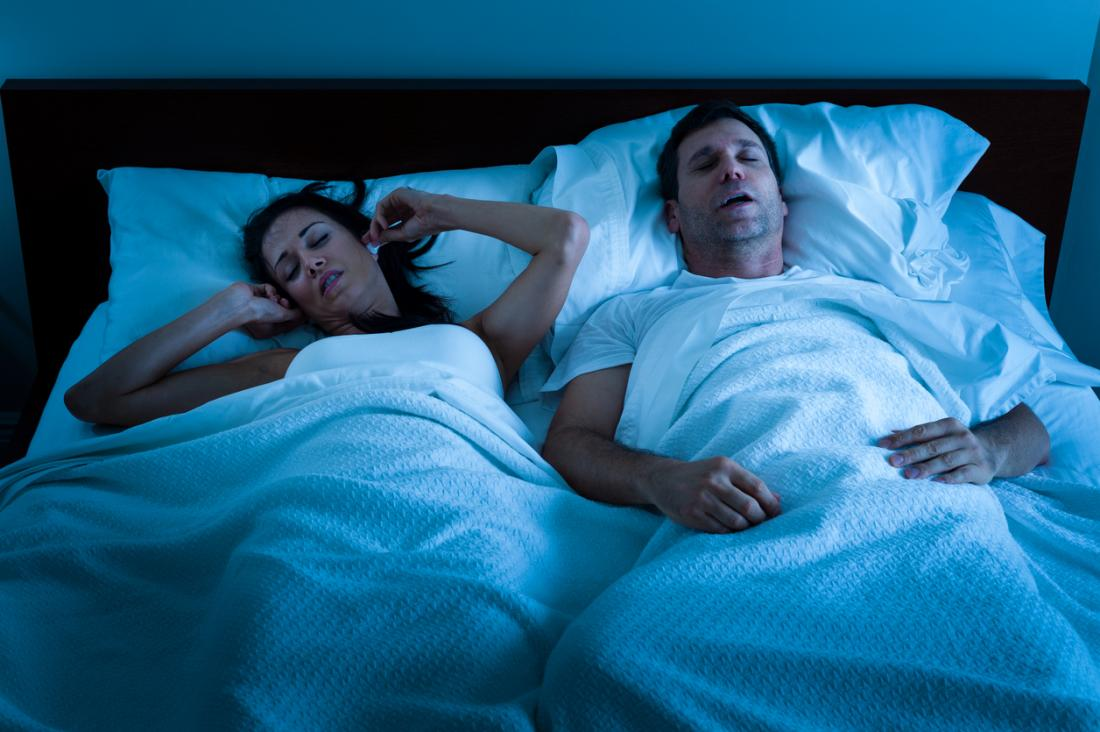 女性が悩まされている間にベッドでいびきを感じる男