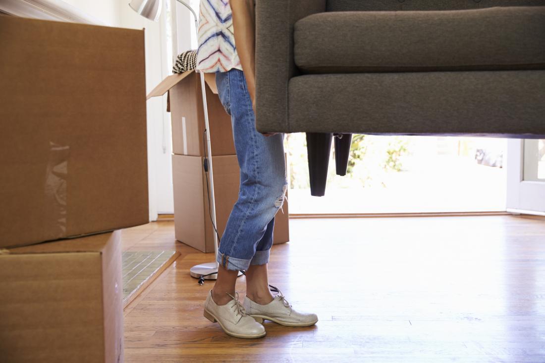 donna che alza un pesante divano