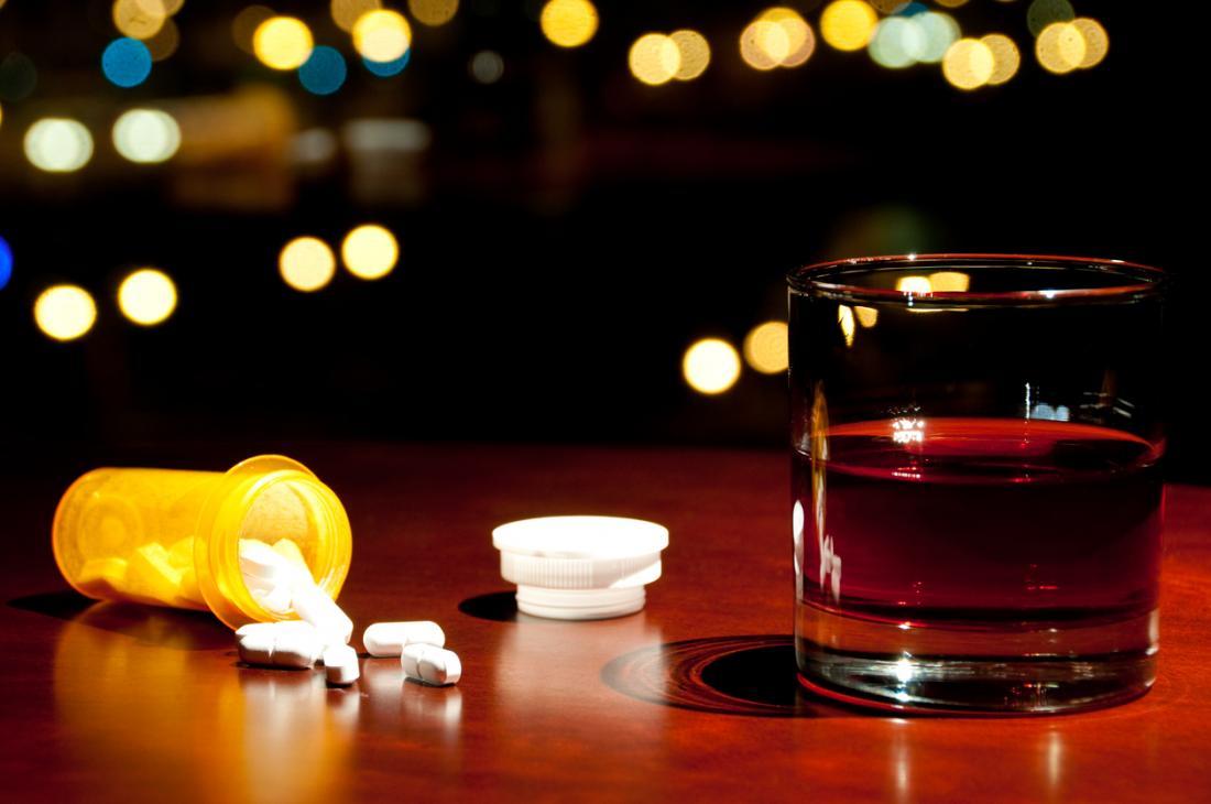 Une bouteille ouverte de pilules à côté d'un verre d'alcool.