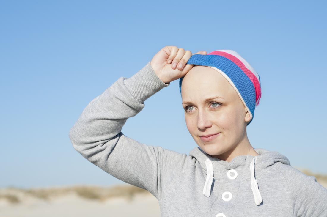 Kahle Frau mit Alopezie draußen mit Hut an.
