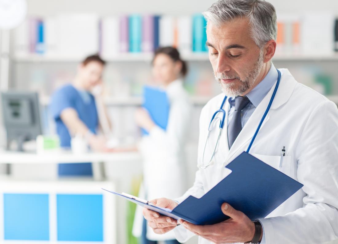 Médico olhando para registros médicos.