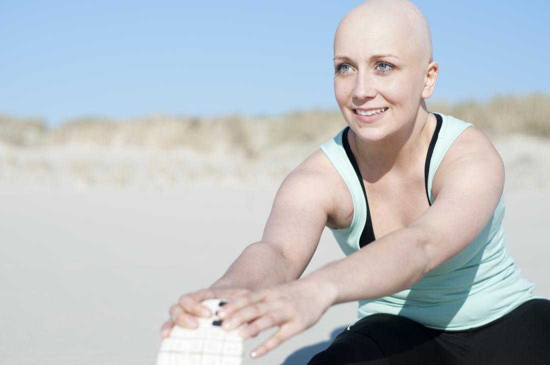 Mulher com alopecia universalis alongamento antes do exercício ao ar livre.