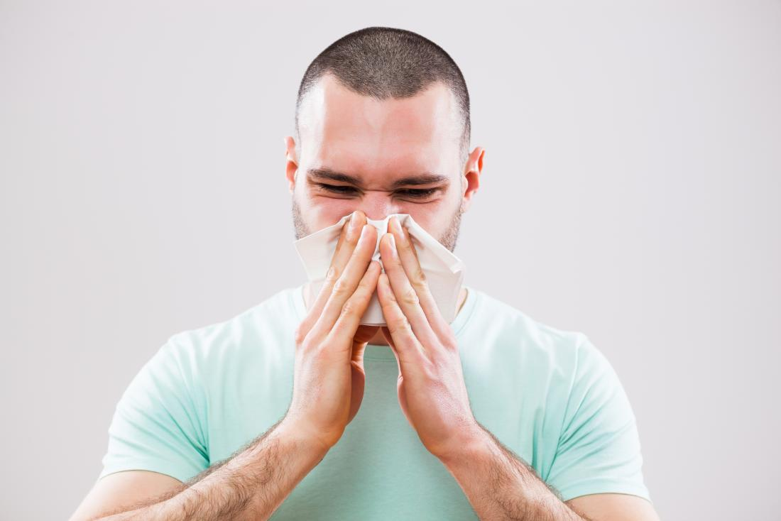 Mann bläst seine Nase in Gewebe wegen einer Erkältung Infektion oder Sinusitis.