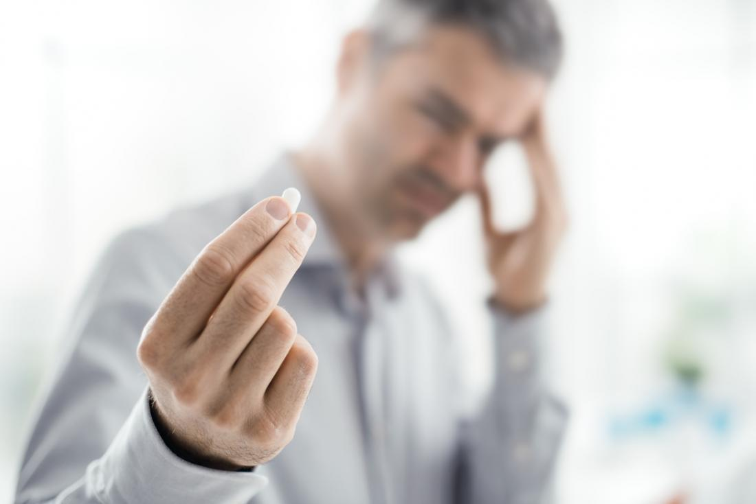 Homem com dor de cabeça, tomando um comprimido