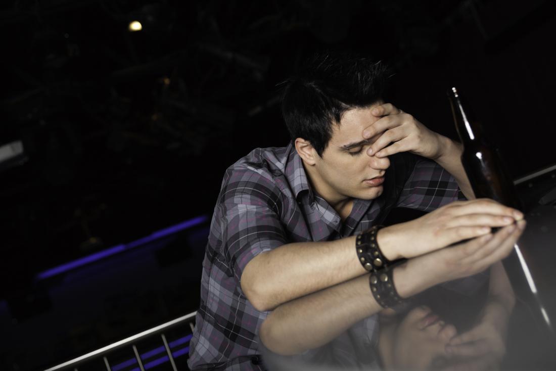 Homme avec de l'alcool dans le bar ou le club tenant la tête à cause de la confusion et des maux de tête.